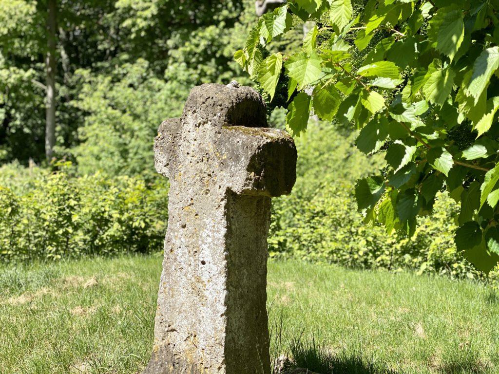 Am Ende des kleinen Labyrinths steht ein verwittertes Kreuz.